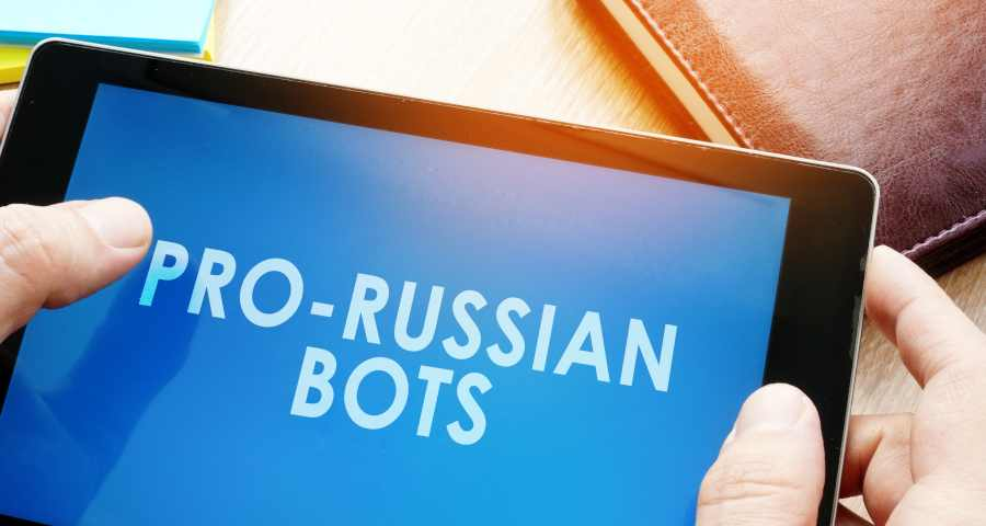 Man holding tablet with words pro-russian bots.