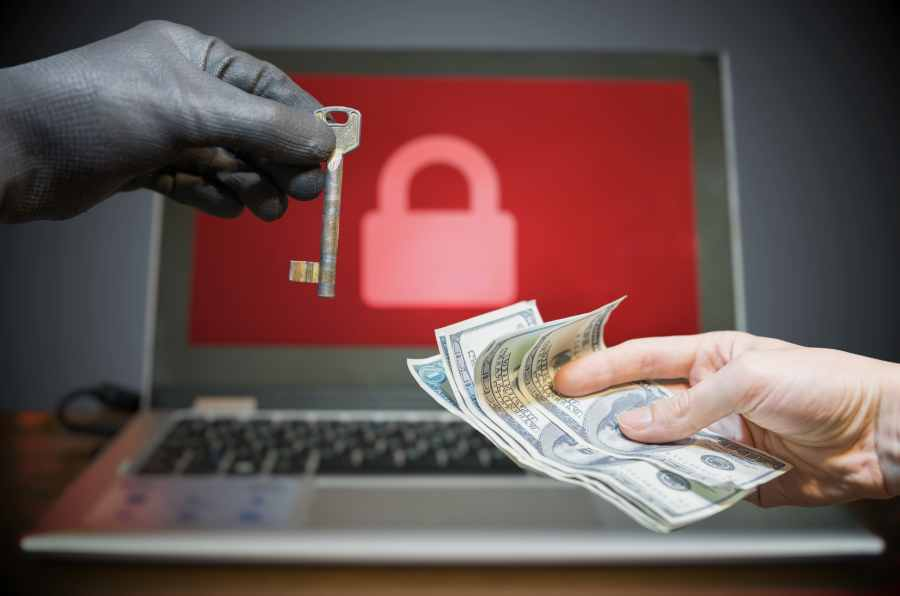 hand handing over cash after device hacked with ransomware
